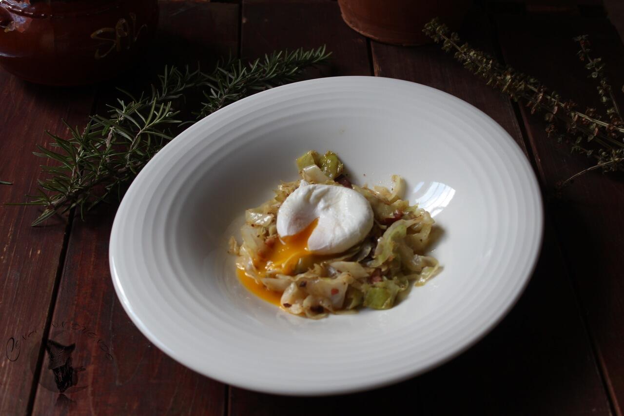 Huevo poché sobre col, cocinada con morcilla y bacon.